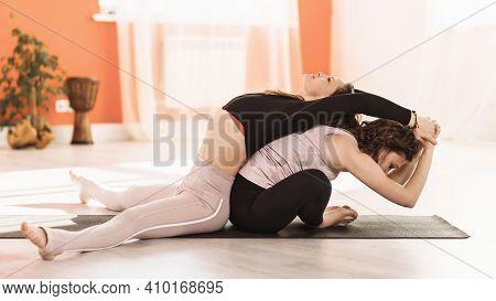 Two Women In Sportswear Practicing Yoga Doing Upavishta Konasana Bending And Baddha Konasana Bending
