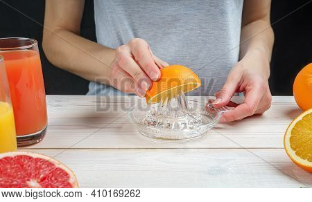 Young Woman Squeezes Orange Juice Using A Manual Glass Juicer