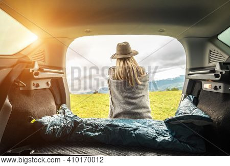 Girl resting in her car, road trip. Woman hiker, traveler camper in sleeping bag, relaxing, drinking hot tea on top of mountain. Road trip. Health care, authenticity.