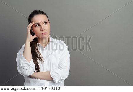 1 White Young Woman 20 Years Old In A White Shirt Stands Thinking On A Gray Background