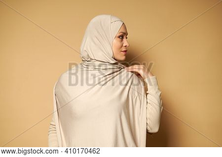 Side Portrait Of Young Serene Muslim Woman Looking To The Side Against Beige Background With Copy Sp