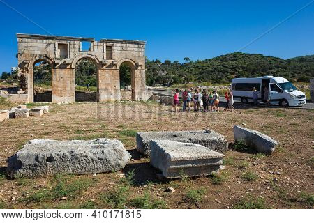 Patara, Turkey - 9 October, 2019: Group of women tourists on a tour to ruins of city gate of Patara (Arch of Modestus) in ancient Lycia on Mediterranean coast. White minivan parked on road
