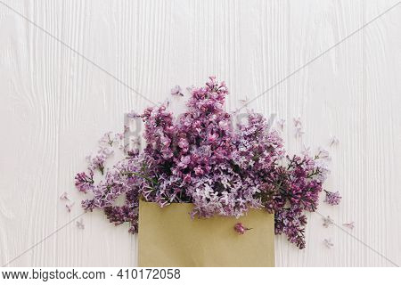 Spring Lilac Flowers Blooming From Envelope Flat Lay. Purple Lilac In Craft Envelope On White Wood W