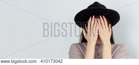 Brunette Girl Covers Her Face With Her Hands, Lifestyle Concept Studio Photo On A White Background.