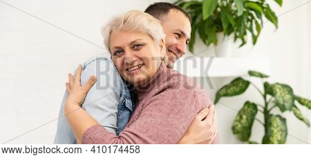 Head Shot Happy Man Embracing Beautiful Smiling Middle Aged Senior Mother In Living Room, Enjoying F