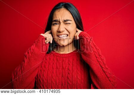 Young beautiful asian woman wearing casual sweater standing over isolated red background covering ears with fingers with annoyed expression for the noise of loud music. Deaf concept.