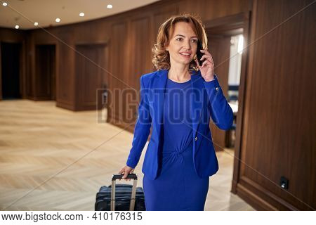 Businesswoman with a suitcase having a call at hotel hallway. Hotel, business, people