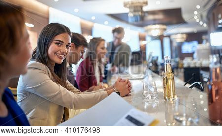 A young businesswoman in the company of colleagues posing for a photo at coffee break in a relaxed atmosphere at the bar. Business, people, bar