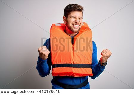 Young blond tourist man with beard and blue eyes wearing lifejacket over white background excited for success with arms raised and eyes closed celebrating victory smiling. Winner concept.