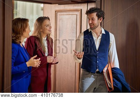 A group of business people having a friendly conversation in a pleasant atmosphere at the hotel hallway. Hotel, business, people
