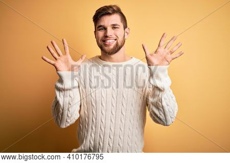 Young blond man with beard and blue eyes wearing white sweater over yellow background showing and pointing up with fingers number ten while smiling confident and happy.