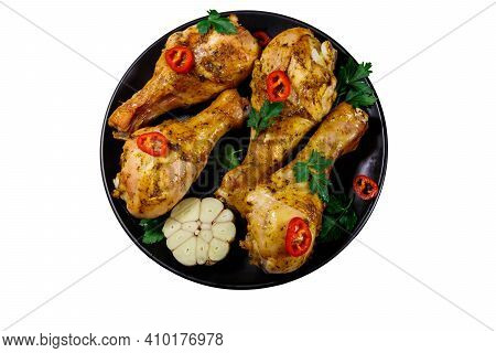 Roasted Chicken Drumsticks With Spices In A Black Plate Isolated On White Background. Top View