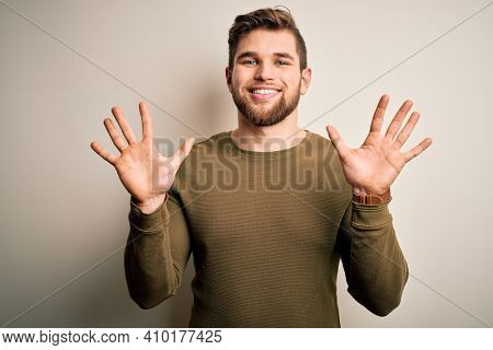 Young blond man with beard and blue eyes wearing green sweater over white background showing and pointing up with fingers number ten while smiling confident and happy.