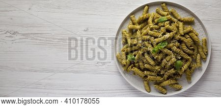Homemade Pesto Twist Pasta On A Plate On A White Wooden Surface, Overhead View. Top View, From Above