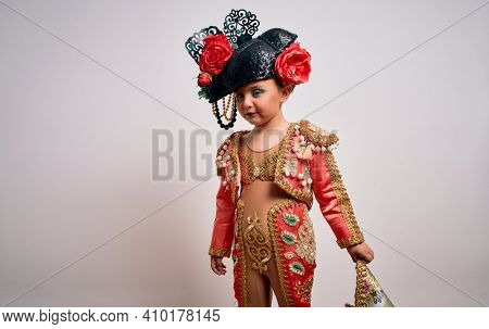 Young little caucasian kid girl wearing  bullfighter traditional folkore spanish suit as carnival costume standing over isolated background