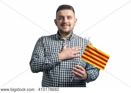 White Guy Holding A Flag Of Catalonia And Holds His Hand On His Heart Isolated On A White Background