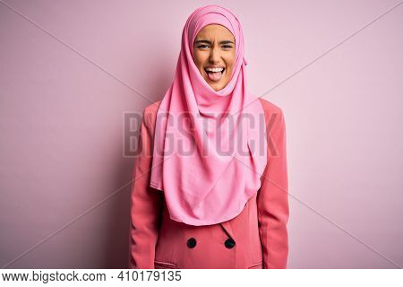 Young beautiful brunette businesswoman wearing pink muslim hijab and business jacket sticking tongue out happy with funny expression. Emotion concept.