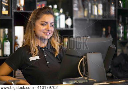 Female Bartender Registrating New Order By Cash-register. A Restaurant Worker Registrating New Order