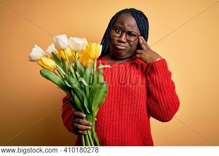Young african american plus size woman with braids holding bouquet of yellow tulips flower Shooting and killing oneself pointing hand and fingers to head like gun, suicide gesture.