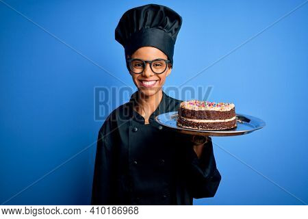 Young african american baker woman wearing cooker uniform and hat holding cake with a happy face standing and smiling with a confident smile showing teeth
