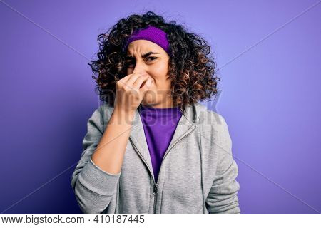 Beautiful curly arab sportswoman doing sport wearing sportswear over purple background smelling something stinky and disgusting, intolerable smell, holding breath with fingers on nose. Bad smell