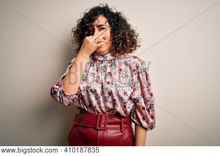 Young beautiful curly arab woman wearing floral t-shirt standing over isolated white background smelling something stinky and disgusting, intolerable smell, holding breath with fingers on nose