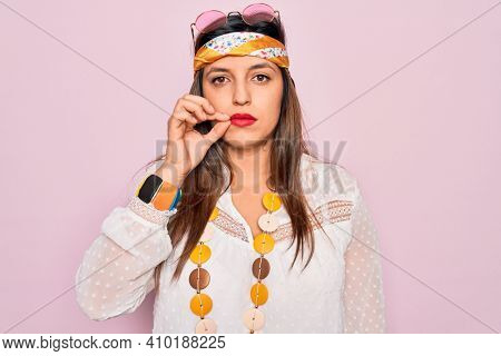 Young hispanic hippie woman wearing fashion boho style and sunglasses over pink background mouth and lips shut as zip with fingers. Secret and silent, taboo talking