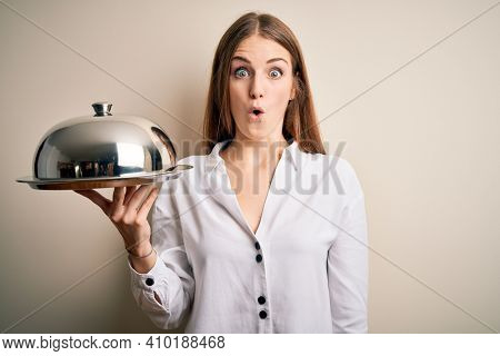 Young beautiful redhead woman holding waitress tray over isolated white background scared in shock with a surprise face, afraid and excited with fear expression