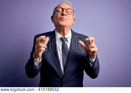 Grey haired senior business man wearing glasses and elegant suit and tie over purple background gesturing finger crossed smiling with hope and eyes closed. Luck and superstitious concept.