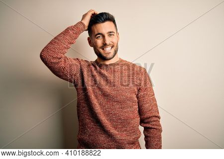 Young handsome man wearing casual sweater standing over isolated white background smiling confident touching hair with hand up gesture, posing attractive and fashionable