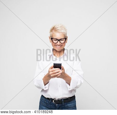 Wow. Phone conversation. Surprised aged woman wearing casual and eyeglasses using phone, isolated over light grey background.
