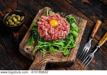 Tartar Beef With A Quail Egg And Arugula Served On A Cutting Board. Dark Wooden Background. Top View