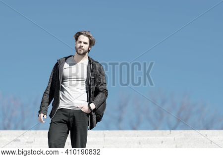 Macho Stand On Blue Sky, Perspective. Man With Beard In Casual Wear On Sunny Outdoor, Fashion. Persp