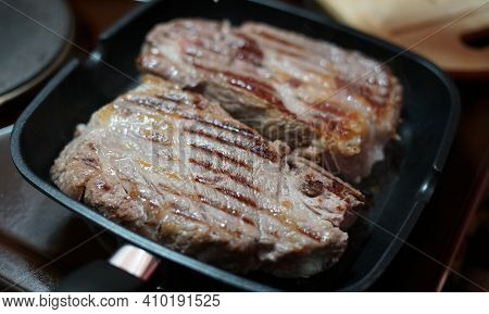 Two Large Pork Steaks Are Fried In A Frying Pan At Home And Adjusted With A Fork. On The Meat, You C