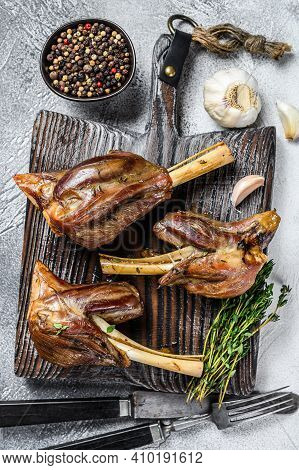 Braised Roast Lamb Shanks On A Wooden Cutting Board. White Background. Top View