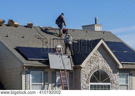 Technician Workers Installing Alternative Energy Photovoltaic Solar Panels On House Roof