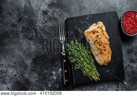 Whole Barbecue Baked Pork Tenderloin. Black Background. Top View. Copy Space
