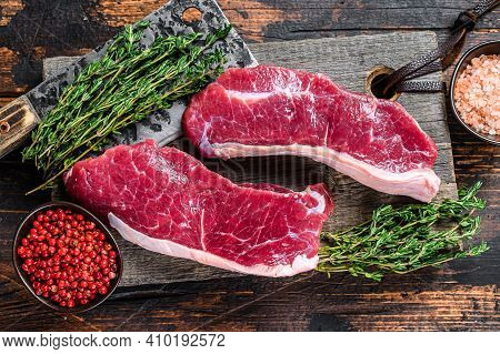 Raw Sirloin Beef Meat Steak On A Wooden Cutting Board With Herbs. Dark Wooden Background. Top View