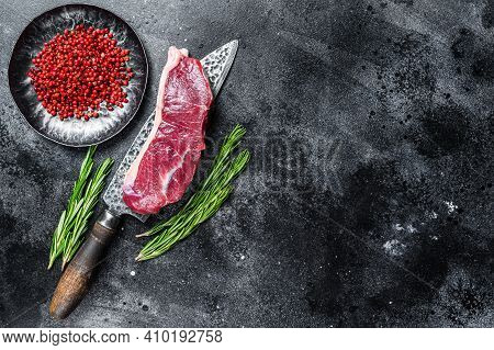Fresh Raw Marbled Beef Meat Sirloin Steak On A Knife. Black Background. Top View. Copy Space