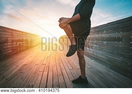 Healthy Young Man Stretching Legs Before Workout Outdoors At Sunset Or Sunrise. Stretching Gluteus M