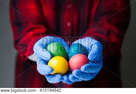 Person Wearing Blue Medical Protective Gloves Holding Colored Easter Eggs, Holiday Amid Global Coron