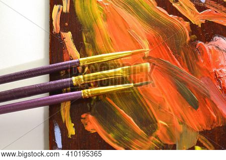 Paintbrushes And Palette With Multi-colored Paints Close Up.