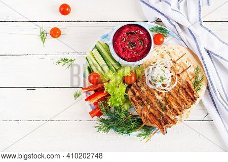 Grilled Chicken Kebab With Beet Hummus And Pita, Fresh Vegetables On A White Table.  Grilled Meat Sk