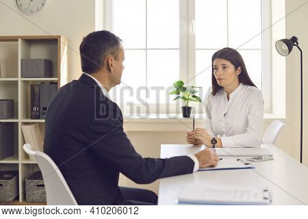 Two Business People Having Business Meeting In Office, Sitting At Desk And Talking