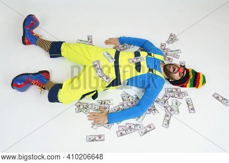 Humor And Fun Concept. A Clown In A Bright Suit Lies On The Floor, His Money Is Around