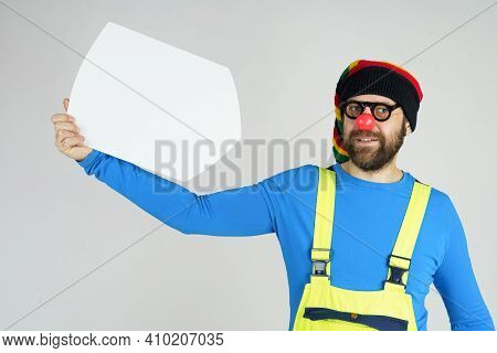 Humor And Fun Concept. A Clown In A Bright Costume Holds A Sign For The Inscription.