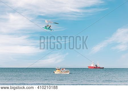 Side View Of The Sea With Pleasure Ships And A Flying Paraglider. Fun Entertainment At The Seaside O