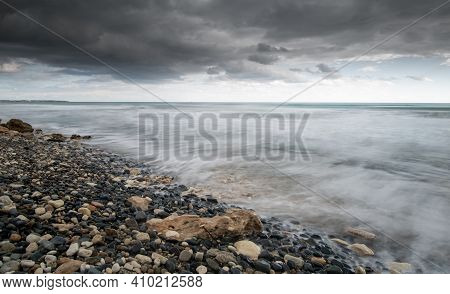 Seawaves Splashing To The Coast With Pebbles Against Stormy Dramatic Cloudy Sky. Wintertime, Longexp