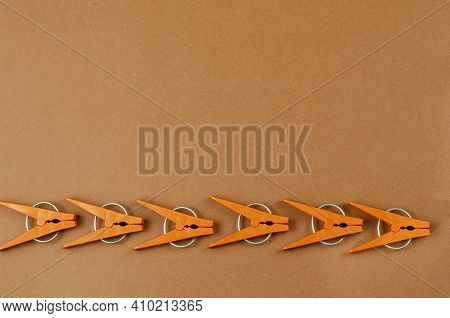 Brown Plastic Clothespins On A Brown Background. A Line Of New Clothespins. Top View, Flat Lay. Copy