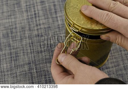 Man's Hand Opens Tea Coffee Tin With Clasp Close-up. Gold Latch Lock Tin For Dry Goods. Selective Fo